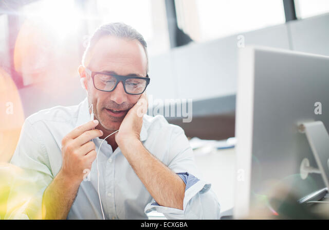 Businessman listening to earbuds at office desk - Stock Image