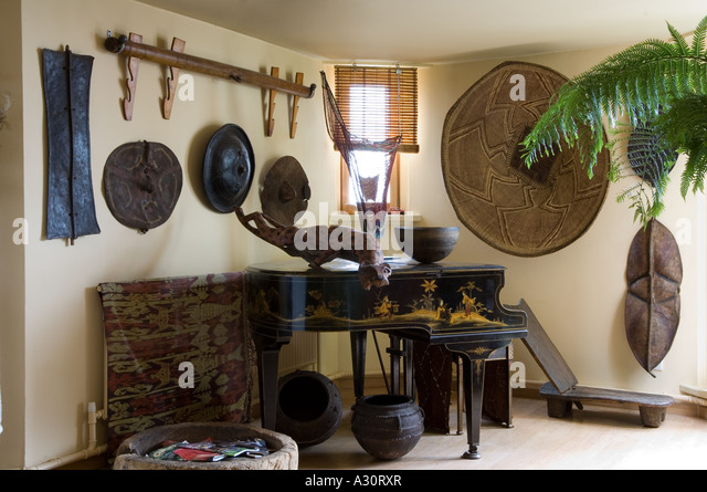 Corner of a room with baby grand piano and African art objects - Stock Image