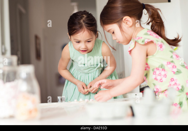 Two young sisters making pastry - Stock Image