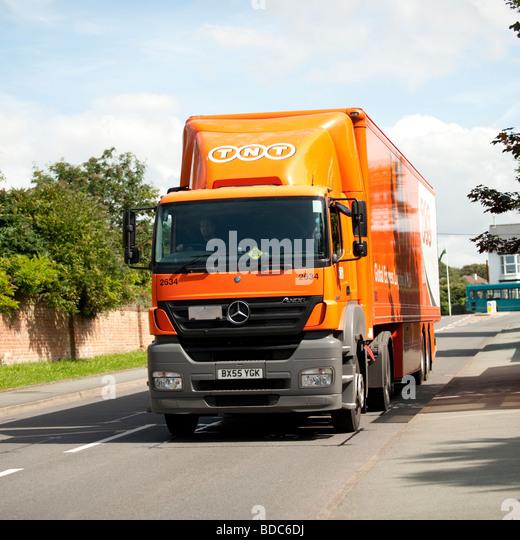 Orange coloured TNT global logistics truck HGV delivery lorry UK - Stock Image