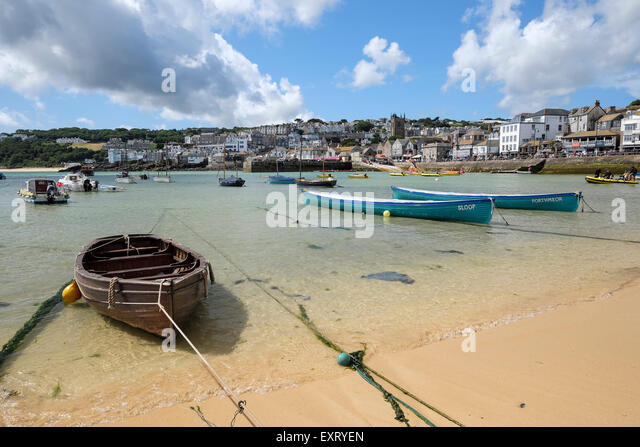 St Ives, Cornwall, UK:  Wooden rowing boat and Gig rowing boats in St Ives harbour with beach in foreground. - Stock Image