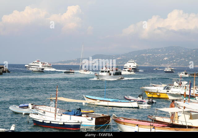The busy and congested harbor of Capri, Italy. Boats rush into and out of the harbor. Italian mainland is in the - Stock Image