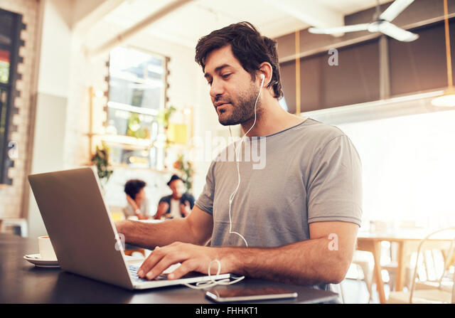 Portrait of a young caucasian man with earphones using laptop at a cafe. Man with beard working on laptop computer - Stock-Bilder