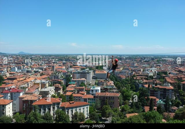 A person zip wiring alongside the historic walls of the Citta Alta (upper city), Bergamo, Lombardy, northern Italy, - Stock Image