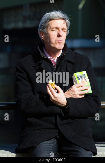 LONDON, UK Worker eating lunch in the sun on the South Bank. - Stock Image