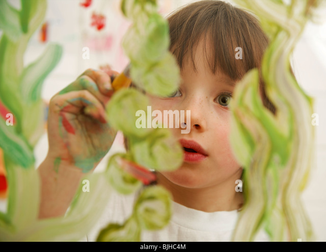 Close up of young girl painting on glass - Stock-Bilder