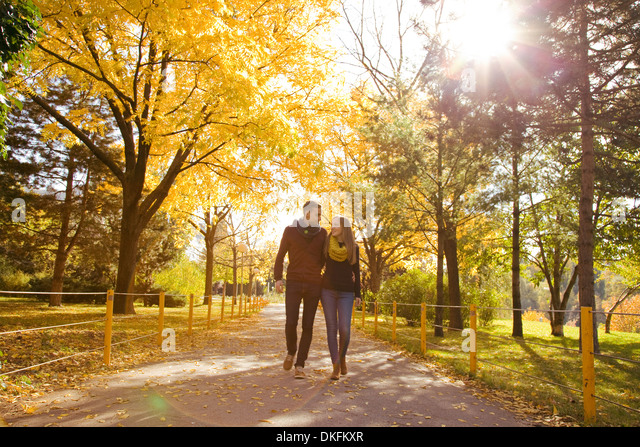 Young couple strolling in autumn park, Vienna, Austria - Stock Image