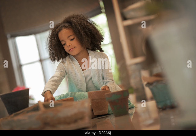 Utah USA young girl planting out seeds in clay pots - Stock Image