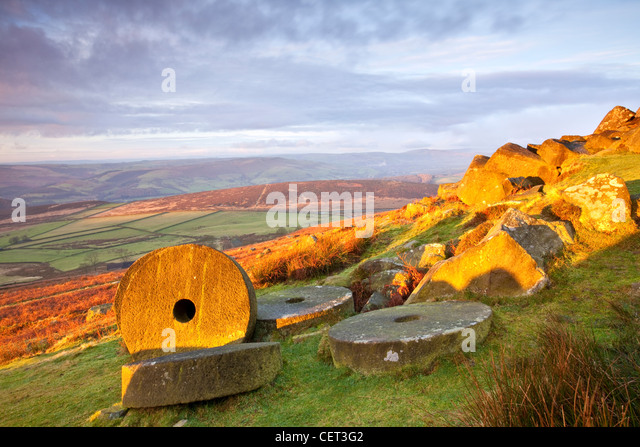 Abandoned millstones beneath Stanage Edge at first light in the Peak District National Park. - Stock Image