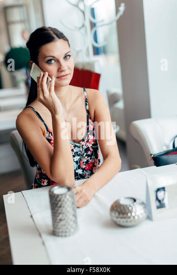 Woman using smartphone in café restaurant and talking - Stock-Bilder