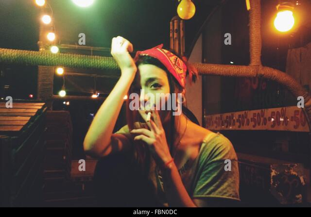 Young Woman With Head In Hand Smoking While Sitting In Illuminated Balcony - Stock-Bilder