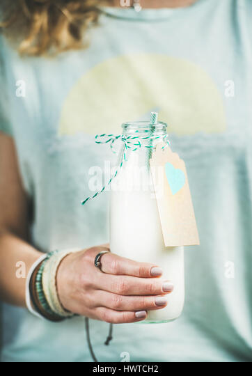 Young woman holding bottle of dairy-free almond milk - Stock Image
