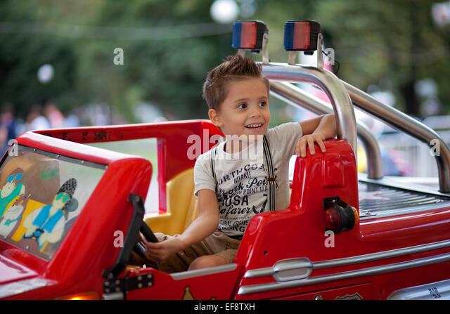 Boy (4-5) driving car in amusement park - Stock Image