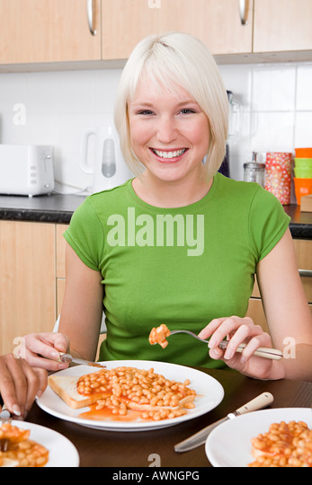 Young woman eating beans on toast - Stock Image