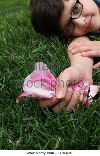 Boy Holding Flower Petals - Stock Image