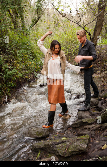 Woman waling across creek with man behind her. - Stock Image