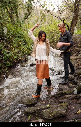 Woman waling across creek with man behind her. - Stock-Bilder