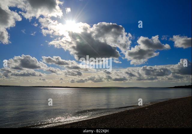Sun through clouds with beach and sea in foreground - Stock Image
