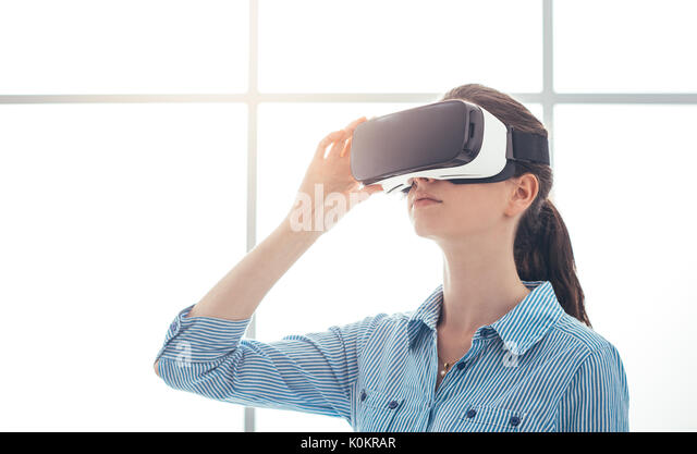 Young woman experiencing virtual reality, she is wearing a VR headset, innovative technology concept - Stock Image