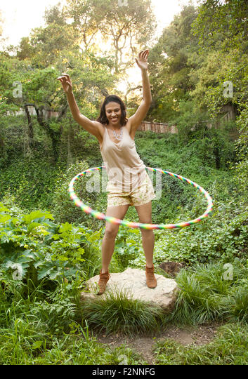 Mixed race woman playing with plastic hoop - Stock Image