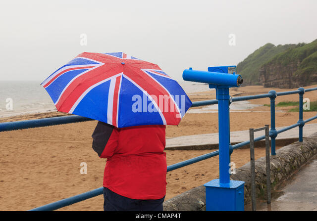 A woman looks out to sea on seafront of deserted seaside with a Union Jack umbrella during very wet British summer - Stock-Bilder