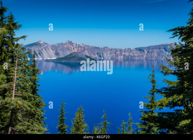 Trees Frame Brilliant Blue Waters of Crater Lake - Stock Image