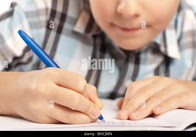 Close up of a schoolboy doing homework, half of face visible and in blur - Stock Image
