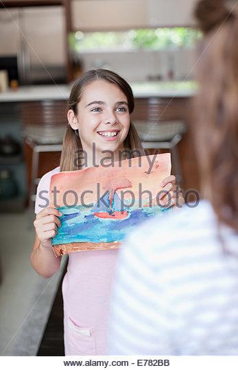 Girl showing mother artwork - Stock Image