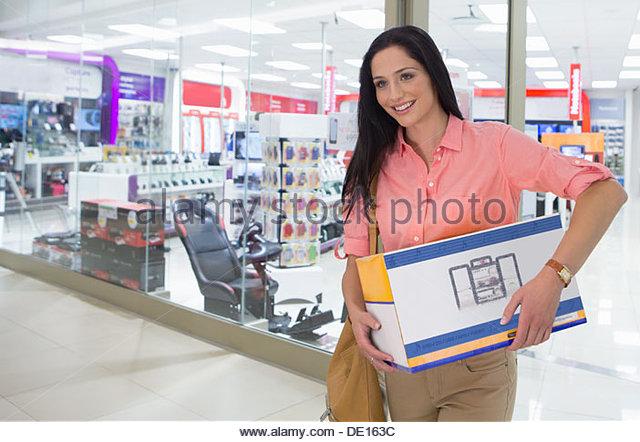 Portrait of smiling woman leaving electronics store with boxes - Stock-Bilder