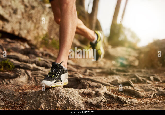 Close-up of trail running shoe on challenging rocky terrain. Male runner's legs working out on extreme terrain - Stock Image