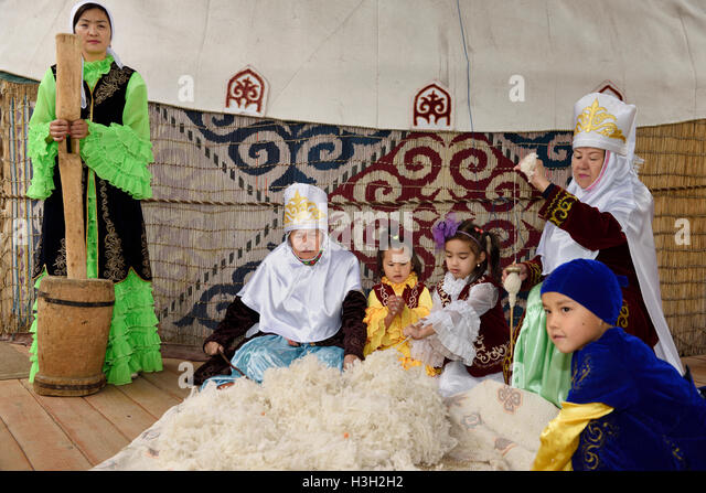 Women and children in traditional Kazakh clothes working wool into felt and yarn Huns Village Kazakhstan - Stock Image