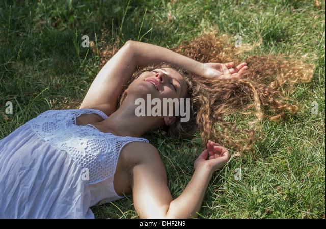 Teenage girl lying on grass, Prague, Czech Republic - Stock-Bilder