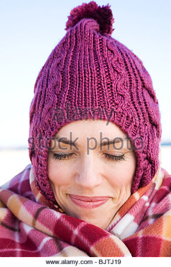 Woman in knit hat and blanket - Stock Image