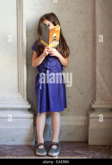 young girl standing in marble lobby reading a pamphlet and looking around - Stock Image