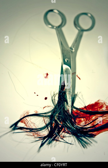 blood-smeared hair with scissors - Stock Image