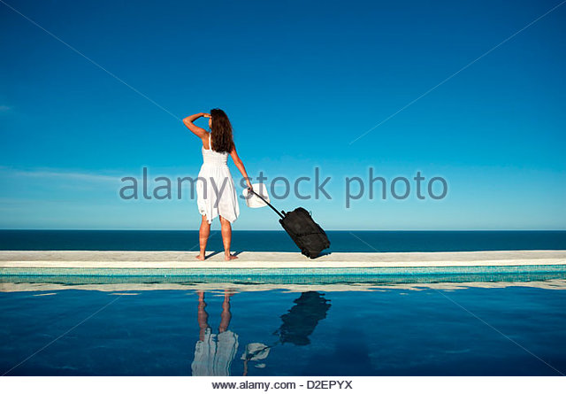 Traveler with heavy baggage walking on a swimming pool with sea view. - Stock-Bilder