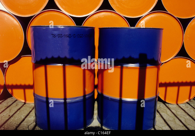 Two upright oil drums painted two colors standing in front of a row of stacked oil drums - Stock Image