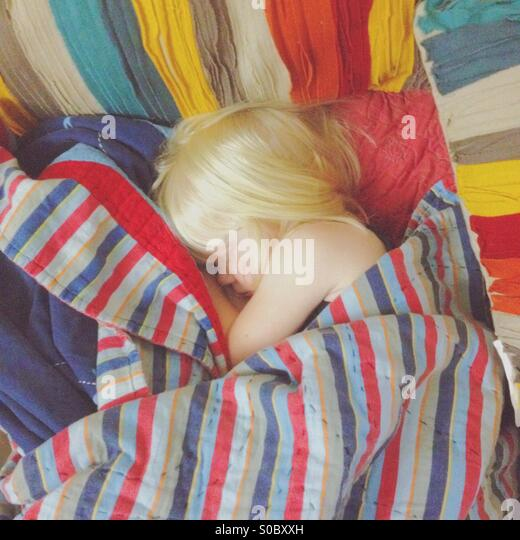 Young blond girl asleep wrapped in a number of brightly colored blankets. - Stock Image