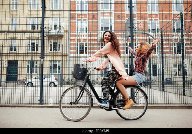 Portrait of two happy young women enjoying bike ride on city street. Female friends riding on one bicycle. - Stock Image