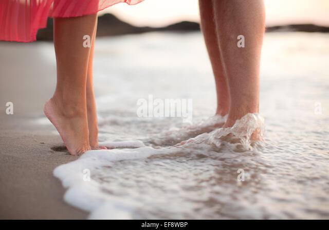 Couple standing in water on beach - Stock-Bilder