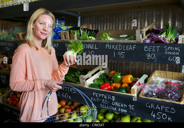 Woman buying produce in store - Stock Image