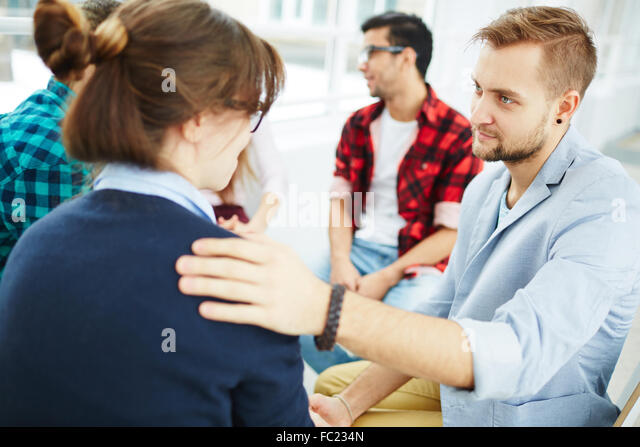 Young man reassuring his groupmate at psychological course - Stock Image