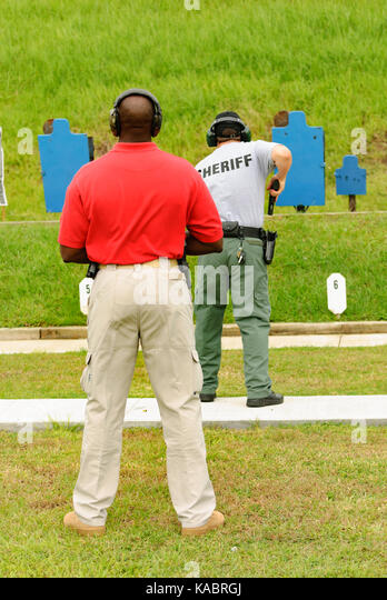 A firearms instructor oversees a law enforcement officer on the shooting range of a training facility in the United - Stock Image