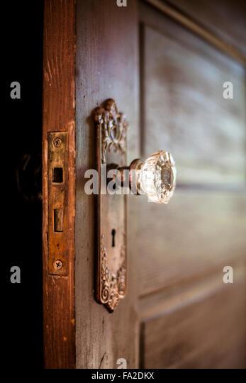 An old door, open with an ornate door knob. - Stock Image