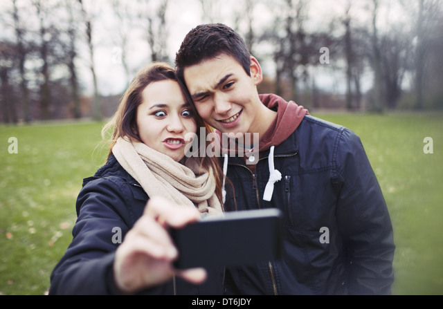 Funny teenage couple photographing themselves with smart phone in the park.  Cute young girl with her boyfriend - Stock Image