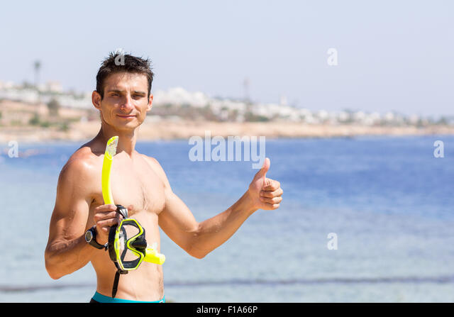 Young smiling man holds snorkeling gear and shows thumb up. Summer vacation background with copy space at right - Stock Image