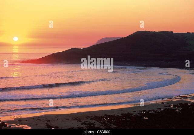 Classic orange sunset over beach .Waves curve into the bay below, sheltered by headlands. - Stock Image