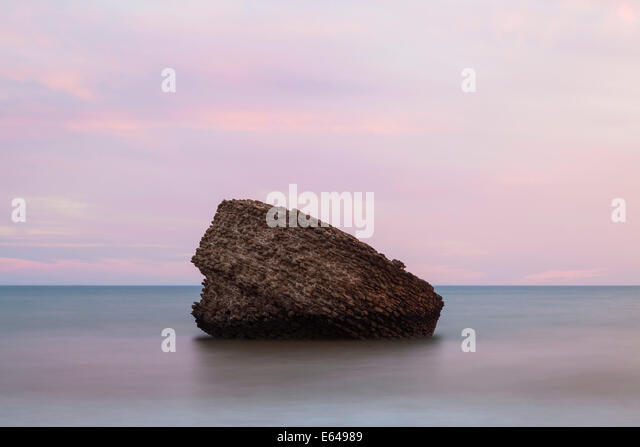 Rock (an old watch tower or beacon) at Matalascañas beach at sunset, Andalucia, Spain - Stock Image