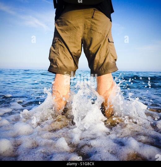 Man's bare legs at the beach, rear view - Stock-Bilder