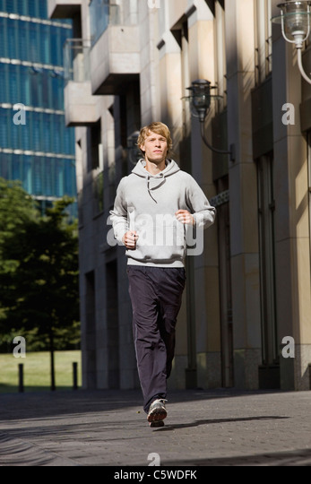 Germany, Berlin, Young man jogging in street, buildings in background - Stock-Bilder